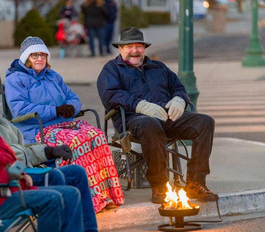 Deb and Dave DeGrendele of Yerington stay warm by their fire while waiting for the parade to start.