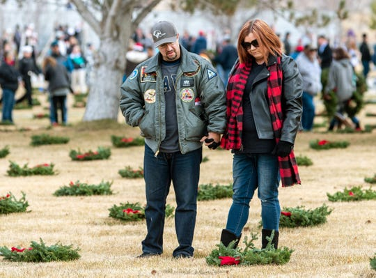 Frank Rivera and Heather Cordell, of Fallon, pause to read a gravesite marker.