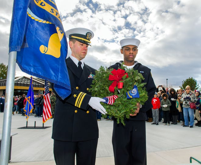 U.S. Navy Lt. Commander Jessie Coe, left, and Sea Cadet Jordan Hannah prepare to lay a wreath honoring Navy veterans.