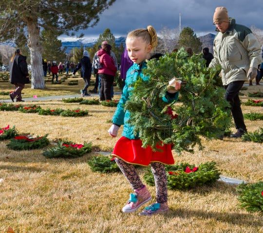 Justice Ryan, 6, of Sun Valley, prepares to place a wreath at a gravesite.