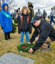 Annalei McFall, 7, of  Fernley Girl Scout Troop 464, and Justin McFall place a wreath at a gravesite.