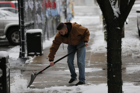 Tristan Flannery clears a sidewalk Monday morning in front of Richmond Furniture Gallery.