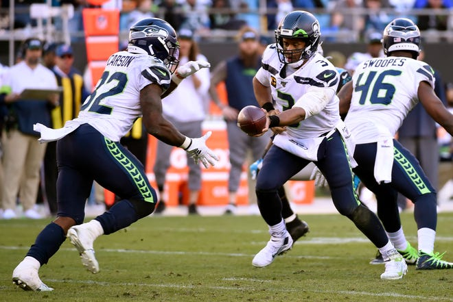 Seattle Seahawks quarterback Russell Wilson (3) hands pff to running back Chris Carson (32) during the second half of an NFL football game against the Carolina Panthers in Charlotte, N.C., Sunday, Dec. 15, 2019.