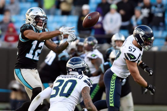 Carolina Panthers wide receiver D.J. Moore (12) reaches for a pass with Seattle Seahawks linebacker Cody Barton (57) and strong safety Bradley McDougald (30) defending during the second half of an NFL football game in Charlotte, N.C., Sunday, Dec. 15, 2019.