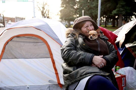 Donna Smith, 61, snuggles with Bubba, her 2-year-old chihuahua, while sitting outside her tent on Commercial St. NE near downtown Salem on Dec. 16, 2019. A camping ban, aimed at clearing city sidewalks and other public property of homeless camps, officially goes into effect on Monday.