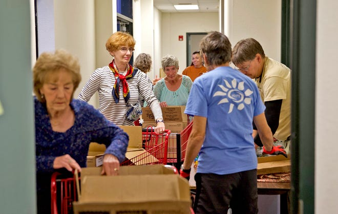 Volunteers at St. Paul Presbyterian Church in San Angelo wait in line with shopping carts to add items to care packages for those in need Friday, Dec. 13, 2019.