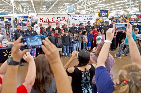 Family members take photos of kids and police officers getting ready to shop at Walmart as part of the Blue Santa event Saturday, Dec. 14, 2019.