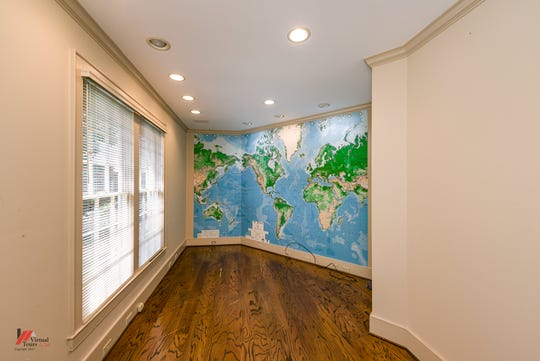 The home office offers a large window overlooking the back patio where one entire wall is a map of the world.