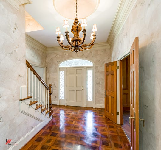 A lavish floor of inlaid wood gleams as light from the lovely transom and diamond patterned sidelights shines through.