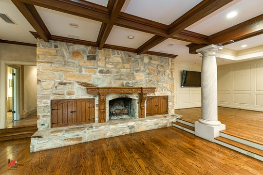 A coffered ceiling and interior columns create a luxurious look, while the oversized stone fireplace gives a warm and casual feel.