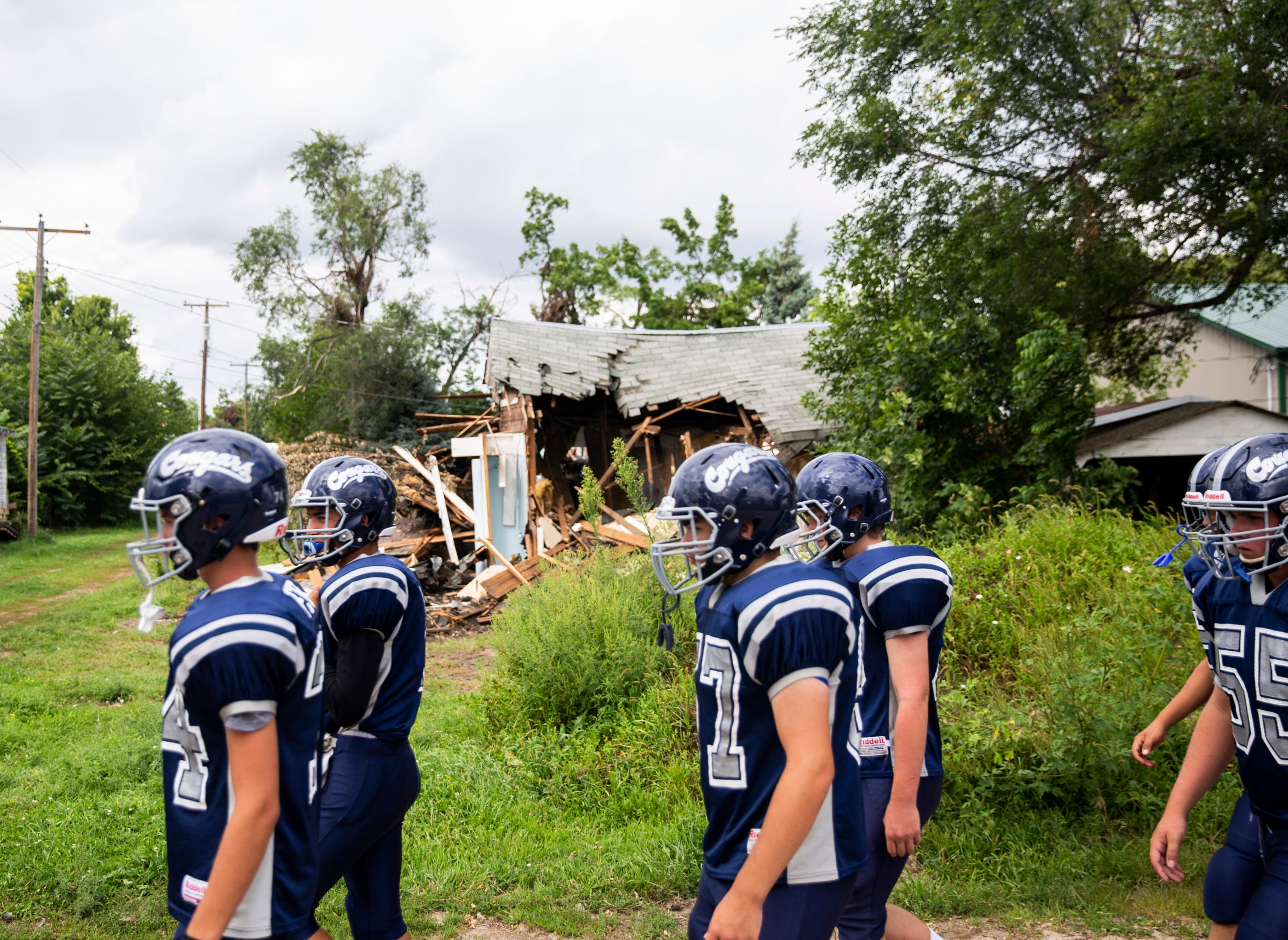 The Burke High School football team walks to Tolstedt field, Friday, Aug. 23 2019 in Burke. A tornado ripped through Burke destroying part of the high school earlier that month.