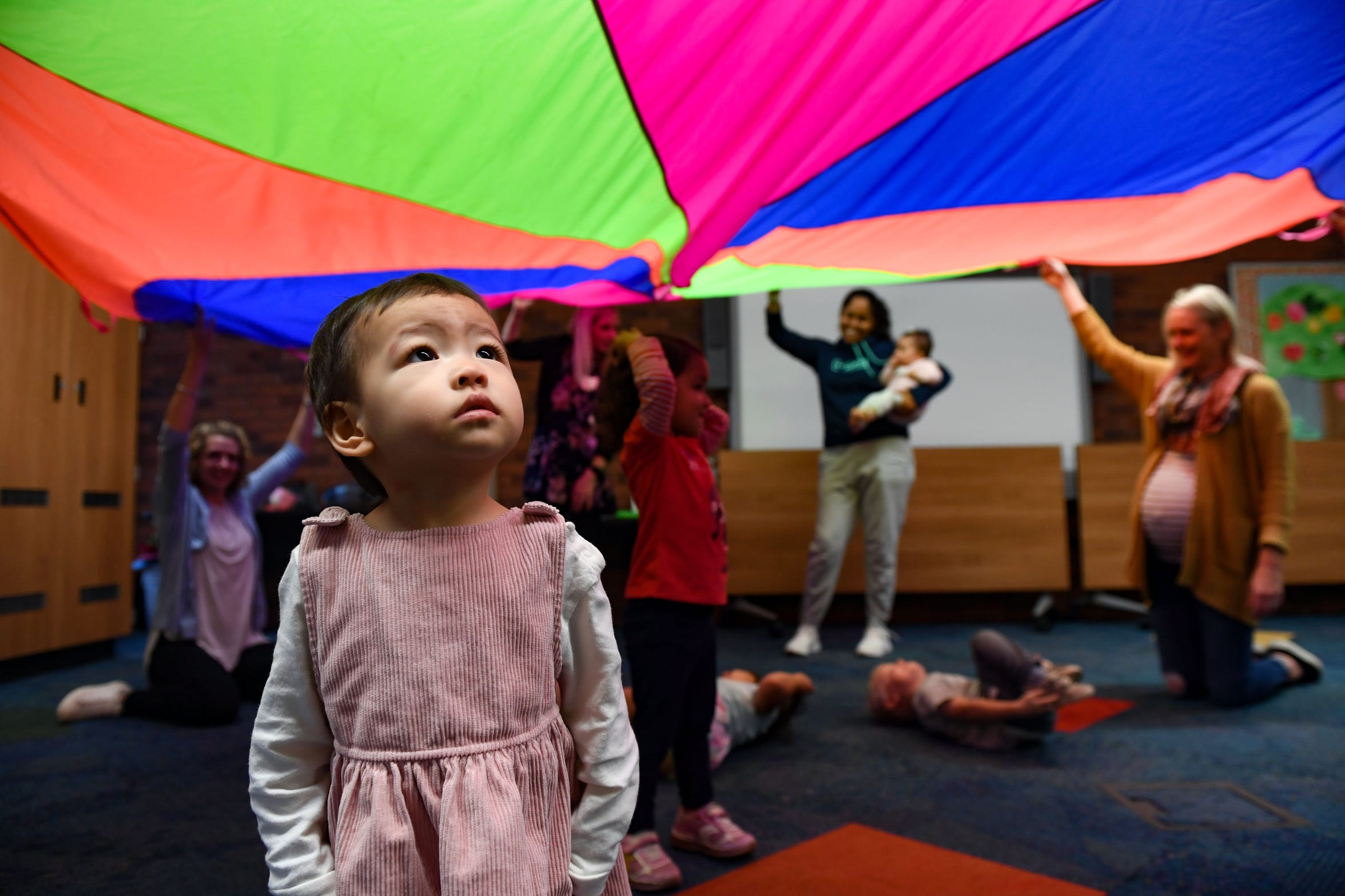 Mila Yang stares in awe at the moving colors of a parachute during a music and movement program on Friday, September 27, 2019 at the Sioux Falls downtown library.