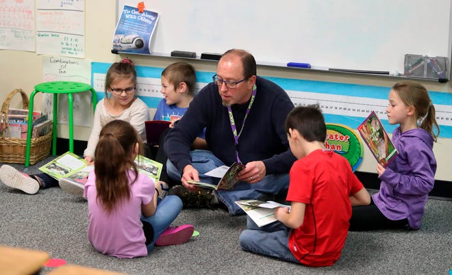 Joel Mann, center, helps Miley Yellow, front left, as they and others in Susan Casper's second grade class at C.C. Lee Elementary School take part in a small group reading exercise Tuesday, Dec. 3, 2019 in Aberdeen, S.D. In the group from the left are: Scarlett Eisenbeisz, Braxton Schwab, Daniel Eyton, front right and Kennedi Artz, far right. Mann has been a volunteer helper for 16 years.