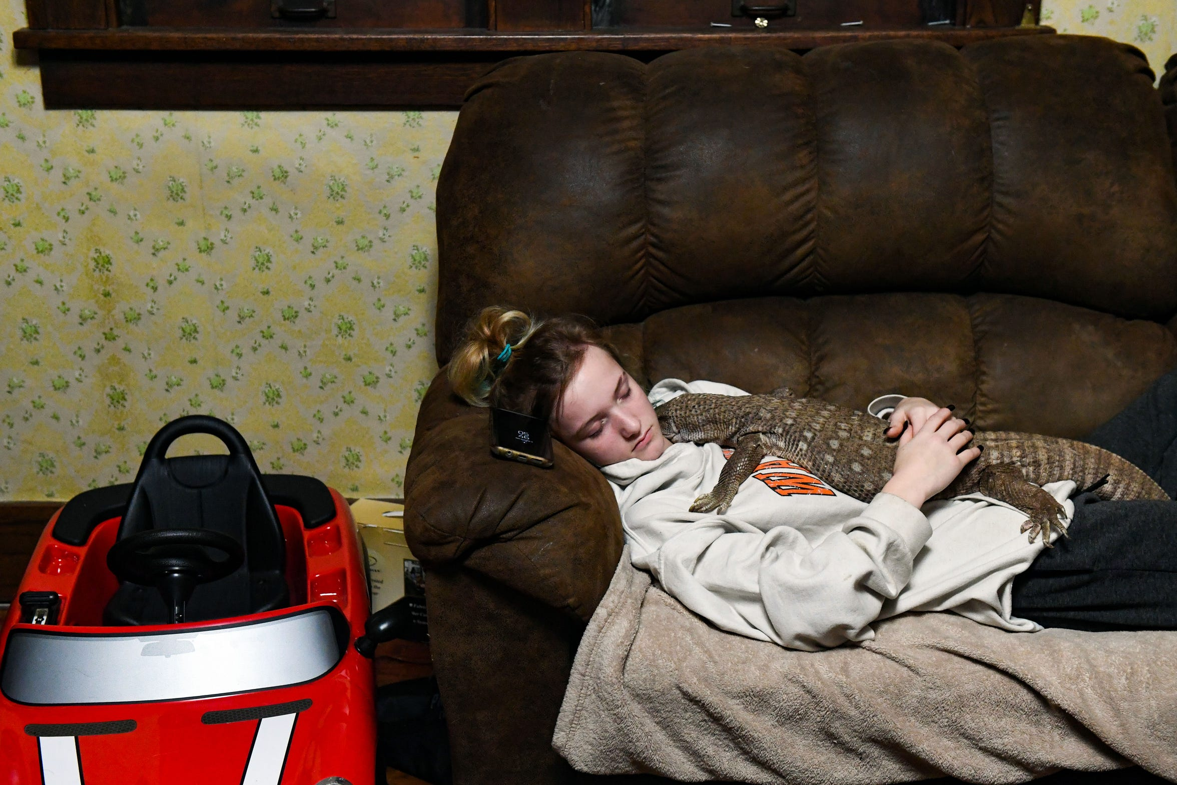 Christina Tinch, 17, naps with Waffles, the family's pet savannah water monitor lizard, on Monday evening, Nov. 18, 2019 at her house in Sioux Falls.