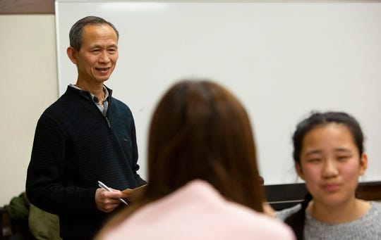 University of Minnesota Zhen Zou listens to students conversing in Mandarin Chinese on Thursday, Nov. 7, 2019. A university program pairs high school students, who've been lifelong learners of Chinese, with Chinese students at the U. (Christine T. Nguyen/Minnesota Public Radio via AP)