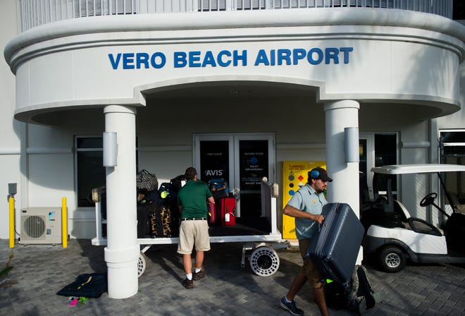 Norberto Montejano (right), of Vero Beach, who works as line service personnel at Vero Beach Regional Airport, unloads luggage for customers arriving on the Elite Airways flight from Newark Liberty International Airport on Thursday, March 17, 2016, in Vero Beach.