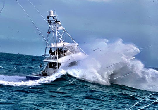 InTents, eventual winner of the Light Tackle Sailfish Tournament, a 62-foot Viking sportfishing boat, takes a huge wave over its bow shortly after departing St. Lucie Inlet Dec. 12.