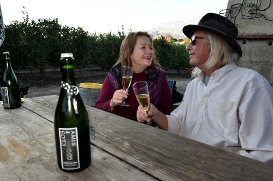 Local winemakers Bruce Freeman, right, and Gretel Compton, of Clos des Amis, have produced Chambang, a sparkling wine made from Ventura County-grown grapes. Bottles are decorated with hand-applied labels and engraved bottle openers attached via strips of polka dot-patterned washi tape.
