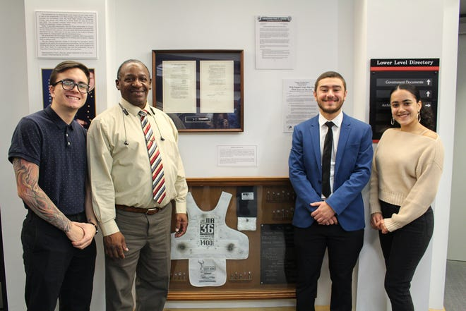 (From left) Students Michael Grossguth of Toms River, Michael Ortiz of Millville, Ricardo Gonzalez of Swedesboro and Margarita Roman of West New York with the exhibit they designed on the Bulletproof Vest Grant law.