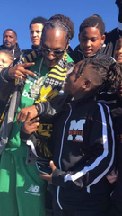 Rapper Snoop Dogg kids around with Reggie Holly of the Millville Thunder Midget football team. The Thunder played two games at the invitational tournament the rapper sponsors every year in California.