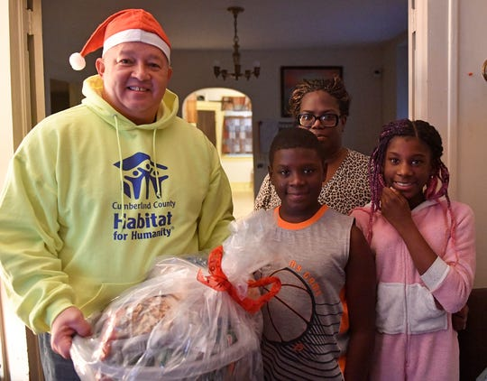 William Gonzalez, a volunteer with Cumberland County Habitat For Humanity, delivers food baskets and gifts donated by the Malcolm Jenkins Foundation to a family in Vineland on Monday, Dec. 16, 2019.
