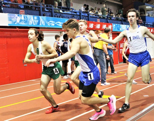 Carmel's Zach Martin takes the baton from Ryan Doherty en route to winning the Section 1 Kickoff 3 boys 4x800 relay Dec. 15, 2019.