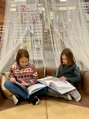 Riley Salan and her sister Adelyn reading in Paige's book tent in the Wichita Falls Public Library's Children's section. Riley is a homeschooled fourth-grader and her sister is a homeschooled first-grader.