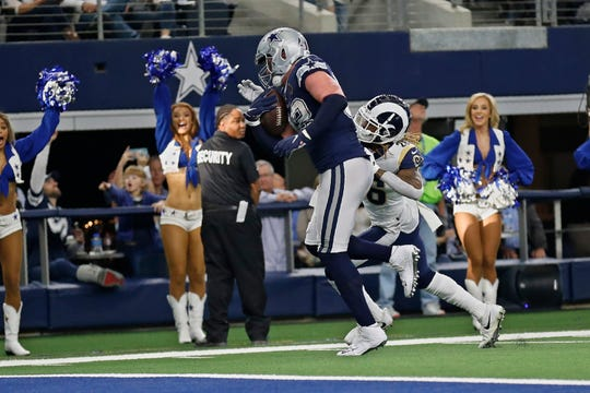 Dallas Cowboys tight end Jason Witten, left, avoids a tackle by Los Angeles Rams defensive back Marqui Christian, right, and carries in for a touchdown in the first half of an NFL football game in Arlington, Texas, Sunday, Dec. 15, 2019. (AP Photo/Roger Steinman)
