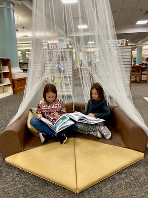 In this file photo, Riley Salan and her sister Adelyn read in Paige's book tent in the Wichita Falls Public Library's Children's section. A Brainly survey found Texas was number one for students who read more this summer than in 2019. At least 83 percent of Texas respondents said they read more full-length books in 2020 than the previous year.