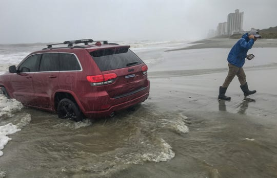 "A television reporter walks away from a Jeep sit stuck in the sand with Hurricane Dorian arriving later in the afternoon in Myrtle Beach, South Carolina Thursday, Septemeber 5, 2019. Police said they were glad the accidentally stuck Jeep was the worst call they responded to, as Hurricane Dorian downgraded from an expected category 4 to a tropical depression. Myrtle Beach Dorian Jeep became the comedic meme on social media for the storm in South Carolina.     ""Dorian Jeep"""