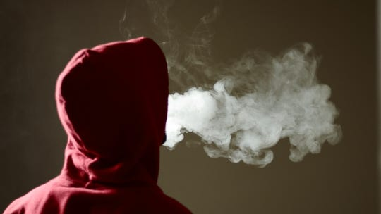 Young male in red hoodie vaping smoking, exhales thick vapor, isolated rear view