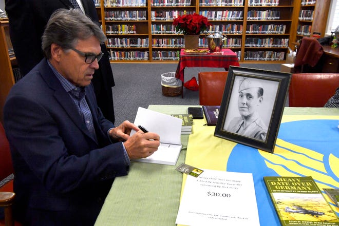 """Former Texas Governor Rick Perry signs a copy of """"Heavy Date Over Germany: The Life and Times of B-17 Tail Gunner Ray Perry."""" Having written the forward, the book is about the former Texas governor's father's experiences in World War II. Perry signed the book, along with his mother, Amelia, and editor Jewellee Jordan Kuenstler, at the Shackelford County Library in Albany on Tuesday. Look for more on the book in Monday's Big Country Journal."""