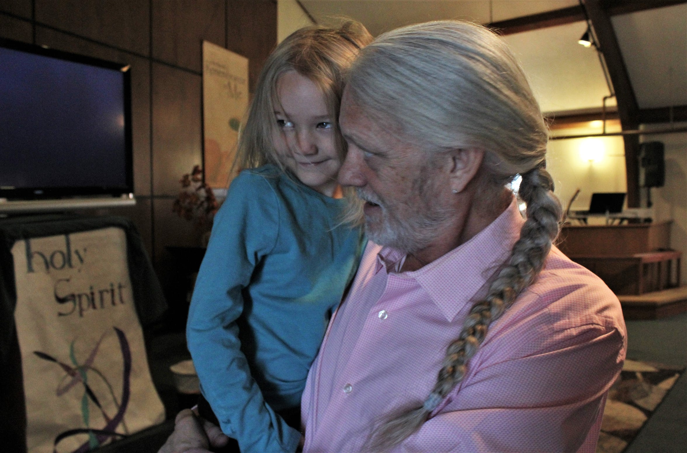 Doug Roysden holds his granddaughter, Cheyenne, before the start of a recent service at Wylie Christian Church, which he has pastored for 18 years. Nov. 10 2019
