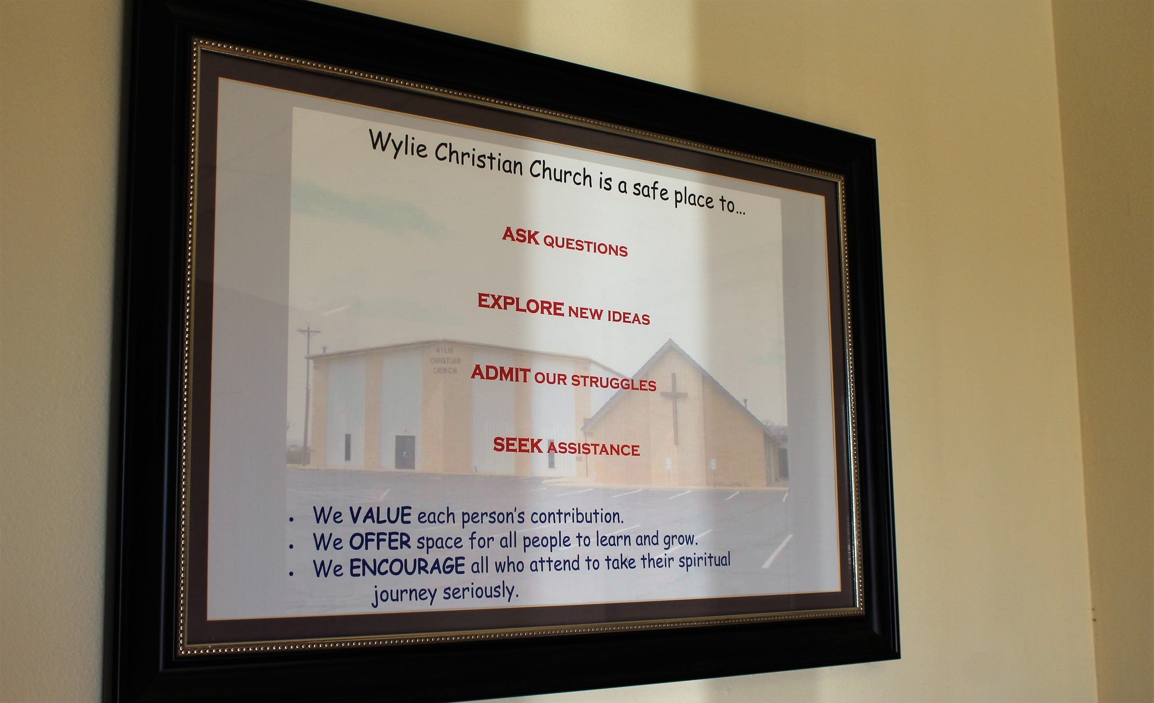 The morning sun illuminates a framed declaration by Wylie Christian Church that it is a safe place.