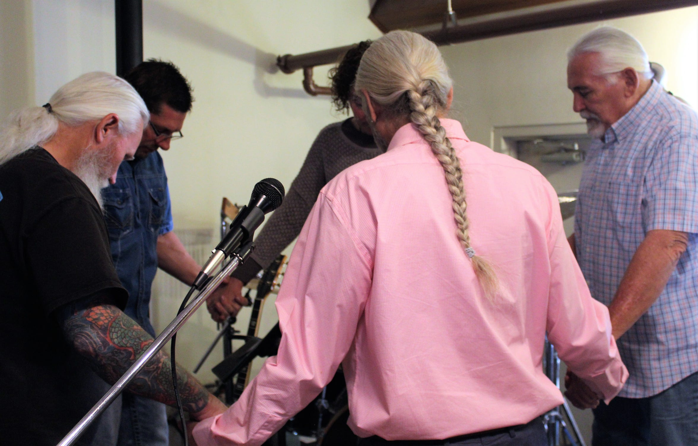 Doug Roysden, in pink shirt, prays with the other members of the Red Dirt Disciples before playing during a recent service at Wylie Christian Church.