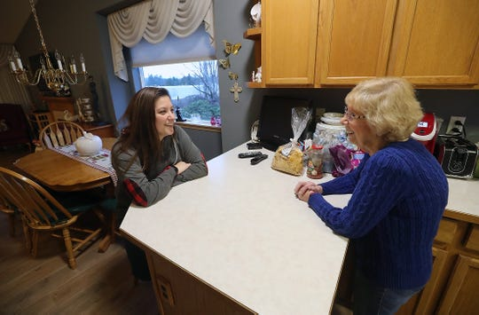 Stacy Leonhardt, left, and neighbor Mary Ann Huntington laugh as they try to decide what to do for dinner in the kitchen of Huntington's home on Saturday. A year after the tornado that hit Port Orchard on Dec. 18, 2018, the Leonhardts and their 5 children are one of the last few families still displaced from their home, and they are staying with Huntington until their house is ready.