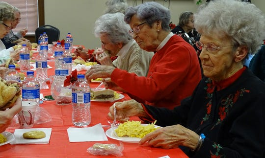 Seniors enjoy their meal at the third annual Christmas party at the Crawford County Council on Aging on Tuesday.