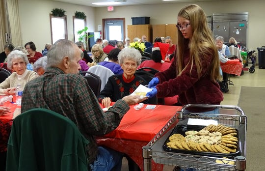 Wayla Sutton, 13, a Bucyrus Middle School student, serves cookies to Larry Hall and Thelma Hawkins, center, during the Christmas party at the Crawford County Council on Aging on Tuesday. Sutton, daughter of activities director Candy Yocum, spent her snow day helping out with the party.