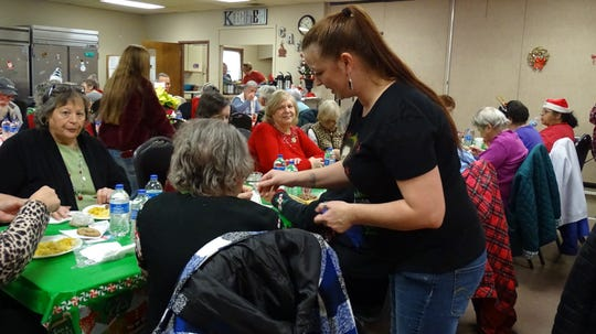 Crawford County Council on Aging activities director Candy Yocum, standing, helps serve meals during the center's annual Christmas party on Tuesday.