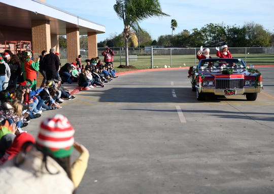 Santa and Mrs. Claus arrive at Hicks Elementary School for the school's Christmas Around the World event, Tuesday, Dec. 17, 2019. The iconic couple arrived in a red Cadillac.