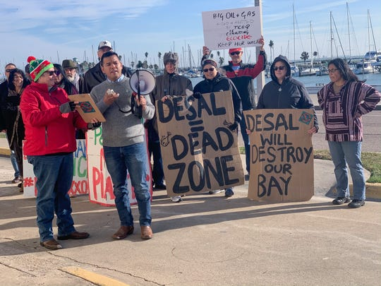 Eric Rodriguez, front, chairman of the Coastal Bend Sierra Club, delivers prepared comments opposing desalination discharge in Corpus Christi Bay. Rodriguez was one of several speakers during a protest Tuesday.
