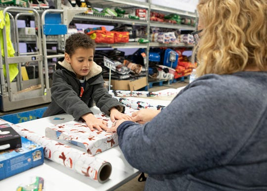 Payton Goldsberry helps wrap the presents he got for his family at the annual after his shopping trip with a local officer for the annual Shop with a Cop at the Chillicothe Walmart on December 16, 2019.