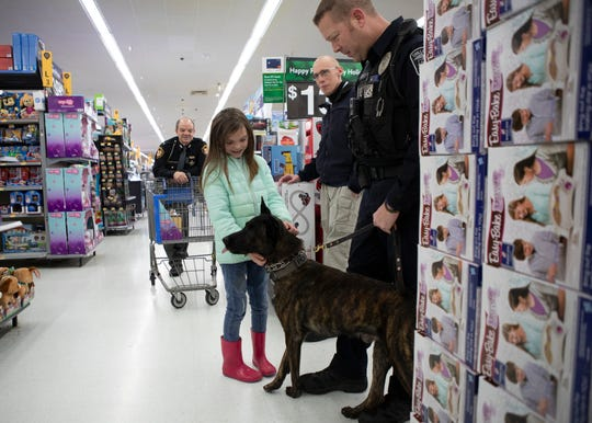Chillicothe police officer Matthew Shipley stops by the Chillicothe Wal-Mart during the annual Shop with a Cop toy event with his police K9 Roo so children like Esme Dehus can meet and pet the loving animal.