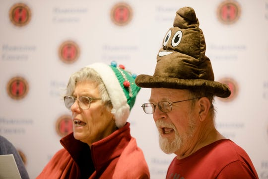 """Joseph Schneider, right, and other members of Communities United For Action sing """"Sewer Carols"""" outside the Hamilton County sewer budget hearing on Tuesday, Dec. 17, 2019, in Cincinnati."""