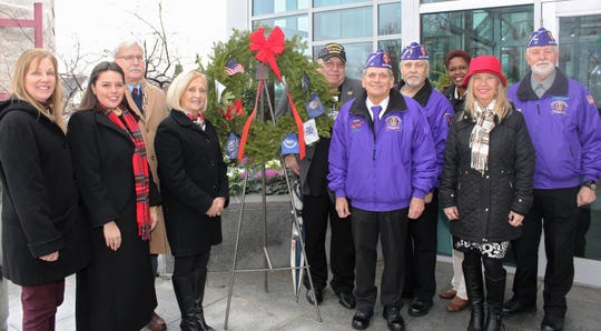 Placing a wreath from Wreaths Across America at the Somerset County Administration Building in Somerville are (left to right) Deborah Rano of the county Veterans Services Office; Freeholder Sara Sooy; Veterans Services Director Peter Niemiec; Freeholder Deputy Director Patricia Walsh; Dom Ragno, RWJ Somerset's veterans liaison; veterans Anthony Del Rocco and Ted Dima, members of Military Order of the Purple Heart Chapter 27; Freeholder Shanel Y. Robinson; Veterans Services Officer Elizabeth Haluszczak; and Joseph Kordzikowski of the MOPH Chapter 27.