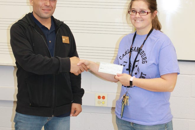 A check in the amount of $4,303 was presented to Laura Née, Music Director at Carl Sandburg Middle School, by Dave Graca, VFW Post 7508 Quartermaster.