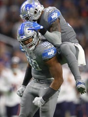 Detroit Lions' Trey Flowers (90) celebrates his sack with Tavon Wilson in the second half against the Chicago Bears at Ford Field on Nov. 28, 2019.