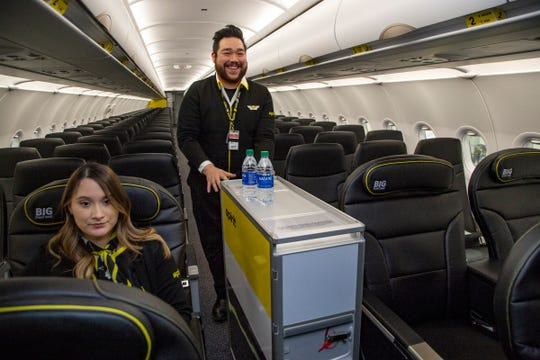 Flight attendants Ale Pedroza, left,  and Ink Kim demonstrate a new beverage cart during Spirit Airlines's tour of its new A320neo aircraft at the airlines' hanger Tuesday at Metro Airport.