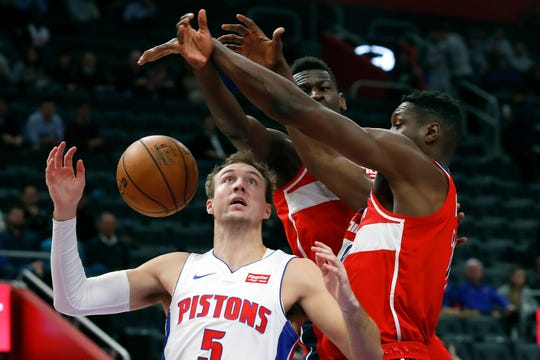 Detroit Pistons guard Luke Kennard (5) drives on Washington Wizards guard Isaac Bonga (17) and center Ian Mahinmi (28) in the first half of an NBA basketball game against the in Detroit, Monday, Dec. 16, 2019. (AP Photo/Paul Sancya)