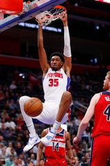 Detroit Pistons forward Christian Wood (35) dunks on Washington Wizards forward Davis Bertans in the first half of an NBA basketball game in Detroit, Monday, Dec. 16, 2019. (AP Photo/Paul Sancya)